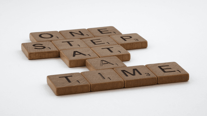 scrabble, scrabble pieces, lettering, letters, wood, scrabble tiles, white background, words, quote, letters, type, typography, design, layout, focus, bokeh, blur, photography, images, image, one step at a time, one day a time, one foot in front of the other, progress, don't give up, persevere, focus, intimidation, every journey, never give up, slow progress, slow and steady, steady as you go