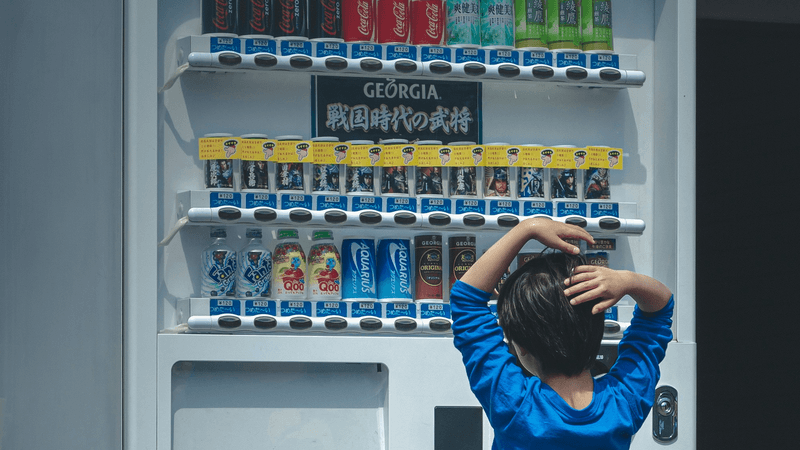 The little boy chooses a drink in the vending machine.